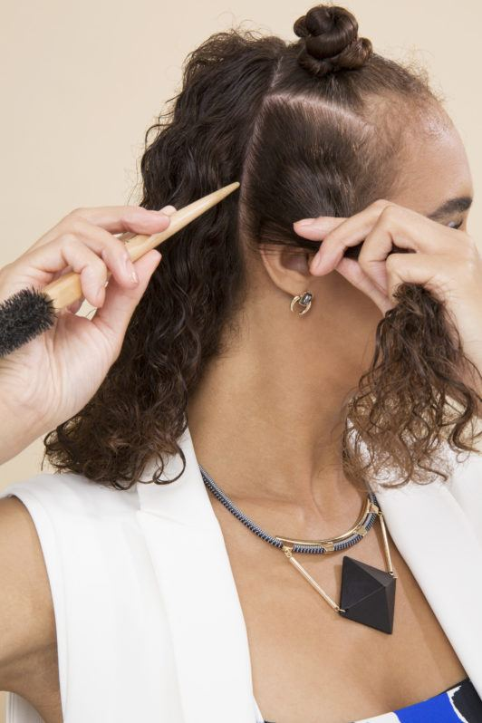 Bantu knots - brown curly haired model sectioning hair using comb