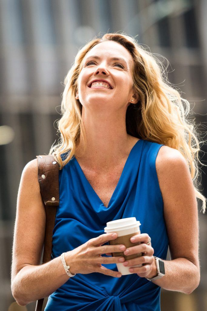 A blonde wavy haired woman over 40 looking at the sky holding a coffe