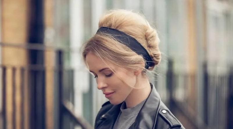 blonde model wearing a leather jacket with her hair in a bouffant french twist with a black headband accessory