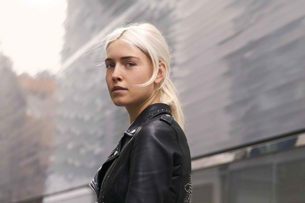ash blonde: image of a woman with an ash, pearl blonde low ponytail, wearing black and posing on the street
