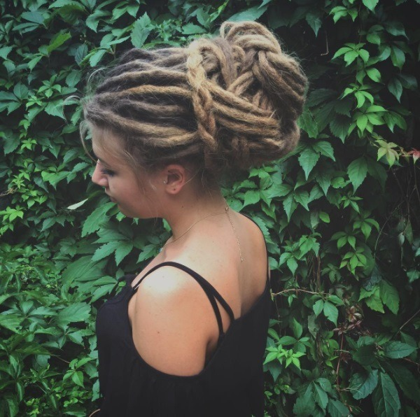 woman with brunette and blonde dreadlocks in a braided bun
