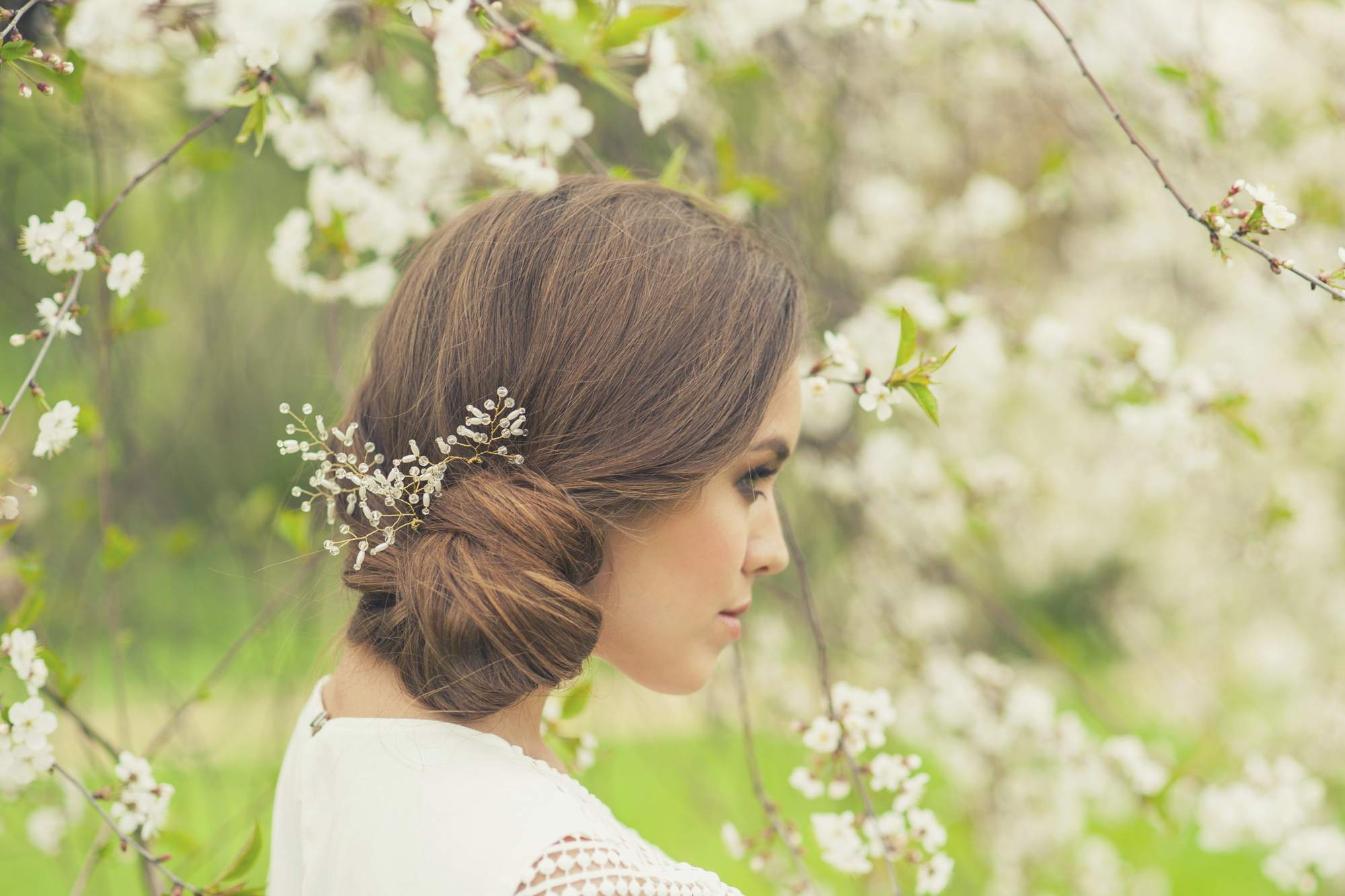 Bridemaids hair ideas include this side bun chignon finished with jewelled hair slide