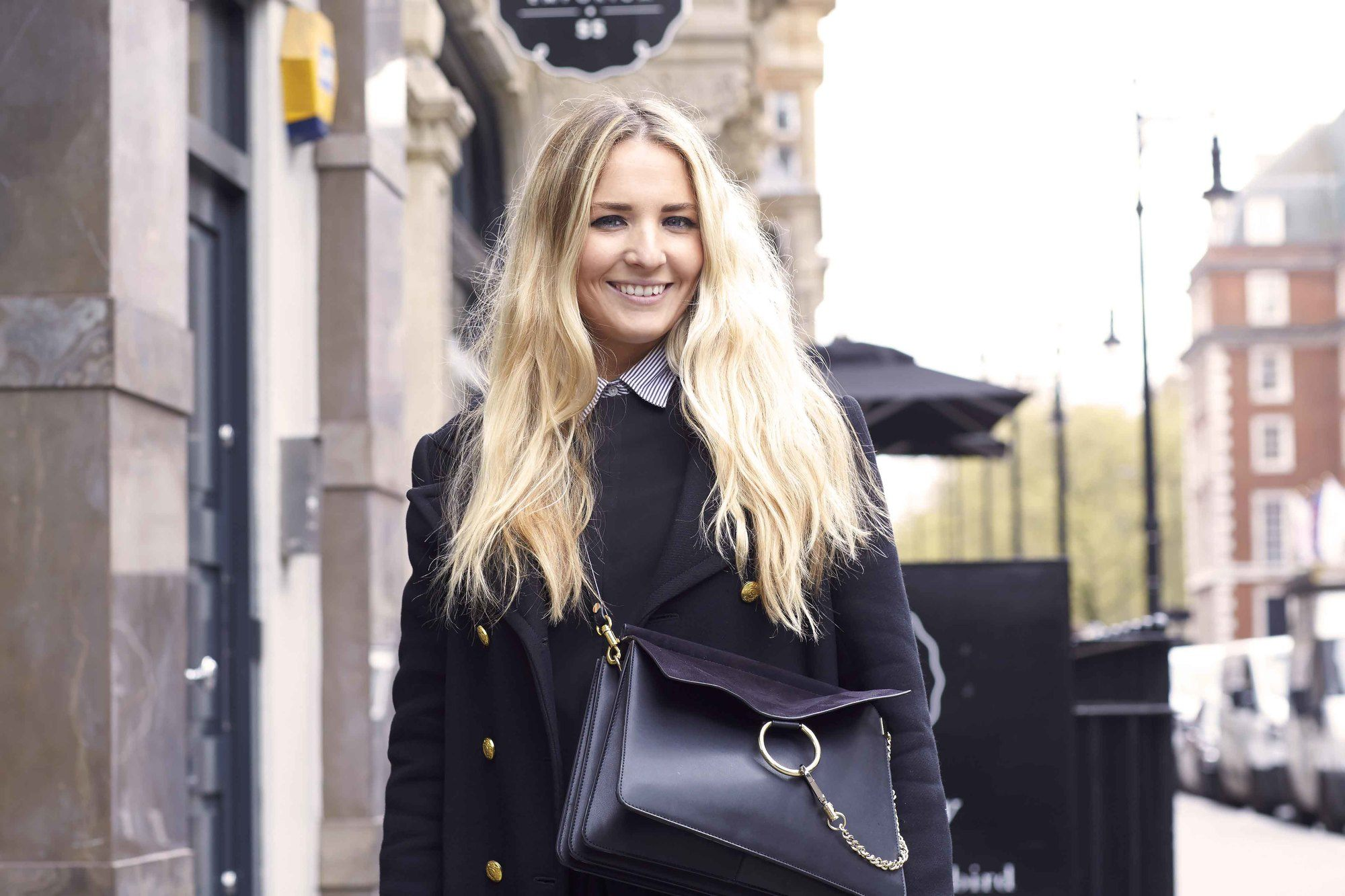 ash blonde: close up shot of woman with long wavy blonde hair, wearing all black and posing on the street