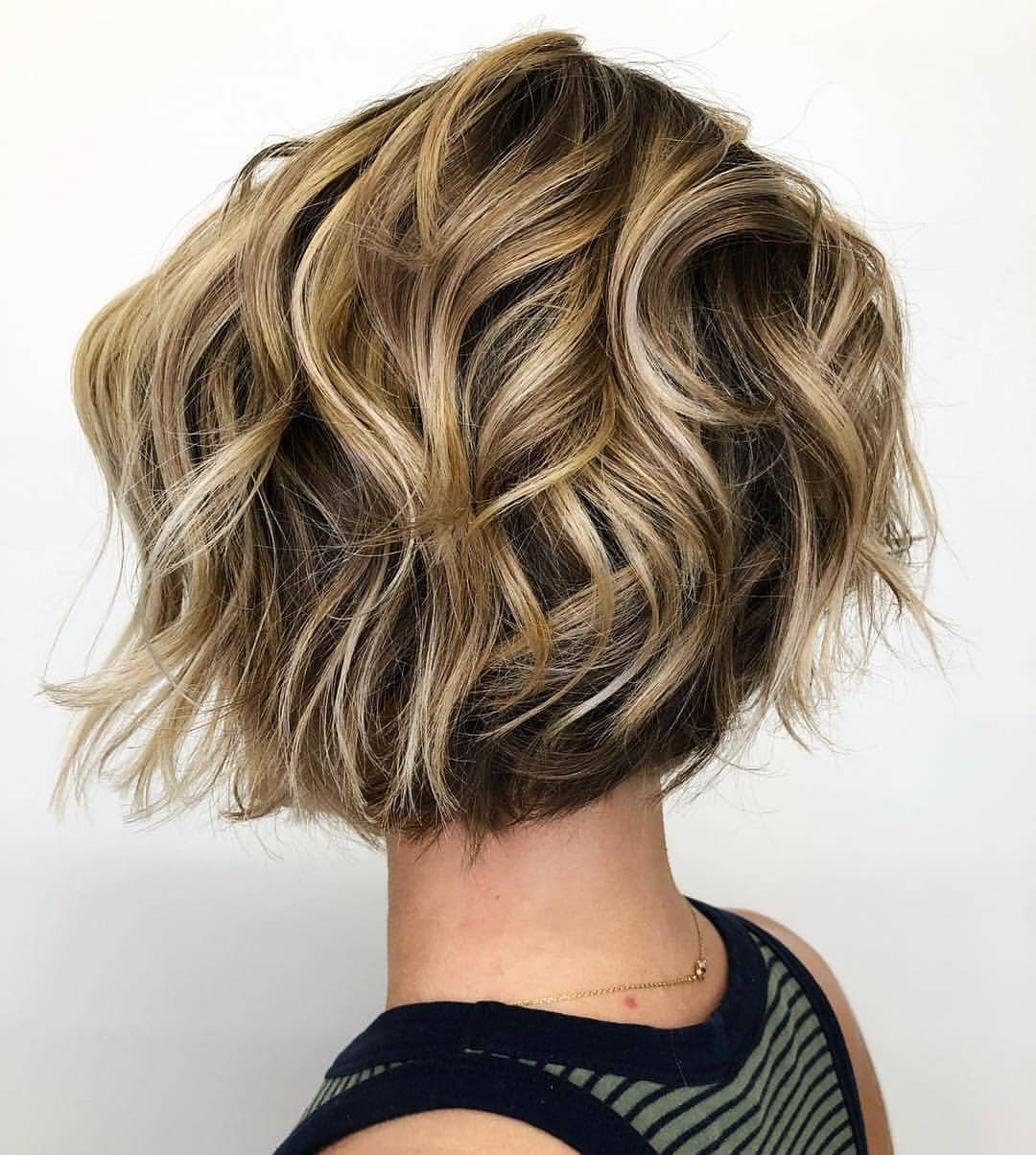 Graduated bob: Woman with short, choppy bronde graduated bob hairstyle in a studio
