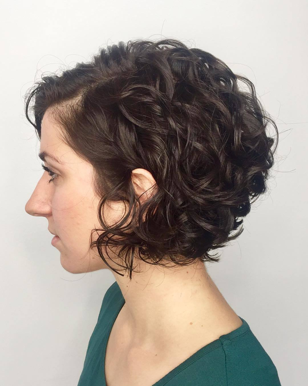 Graduated bob hairstyles: Woman with dark brown curly graduated bob haircut in a studio