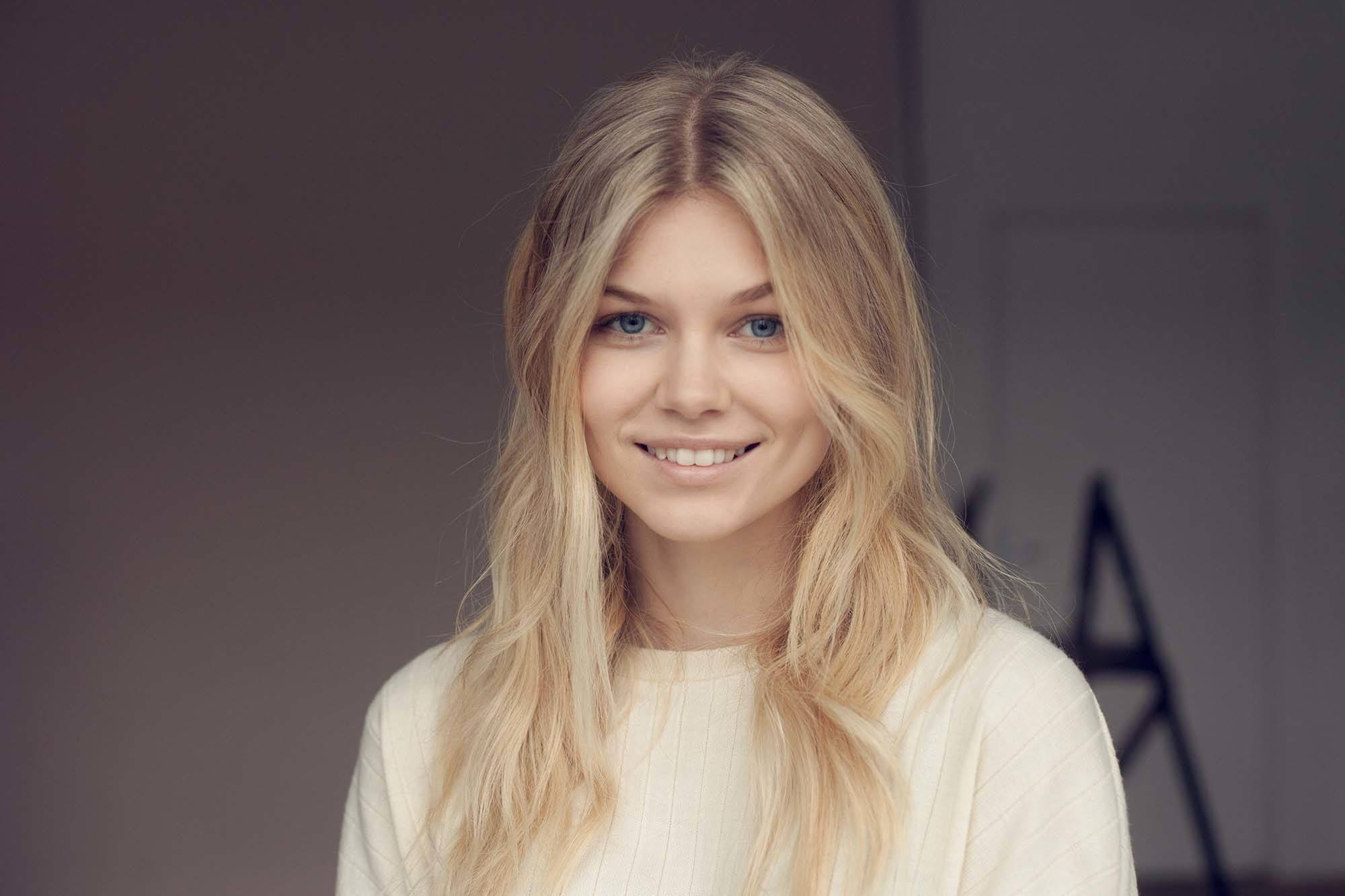 ash blonde hair: close up shot of woman with medium and light ashy blonde hair, styled into waves, wearing white top and smiling
