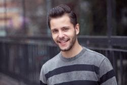 brunette male model wearing a grey and black striped jumper and wearing a quiff hairstyle