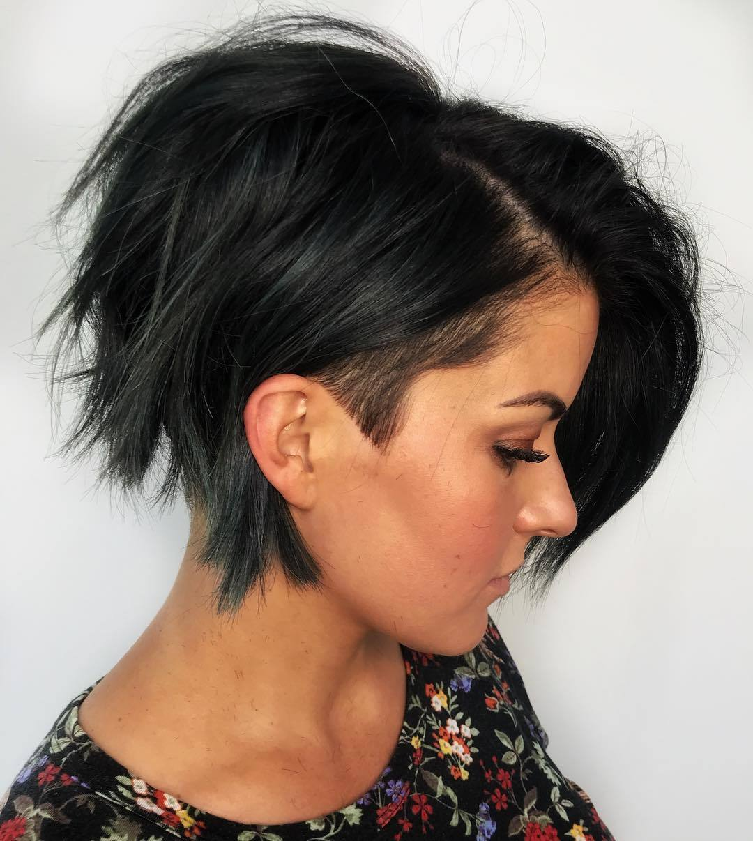 Graduated bob hairstyles: Woman with short graduated emerald green bob with side shaved hair