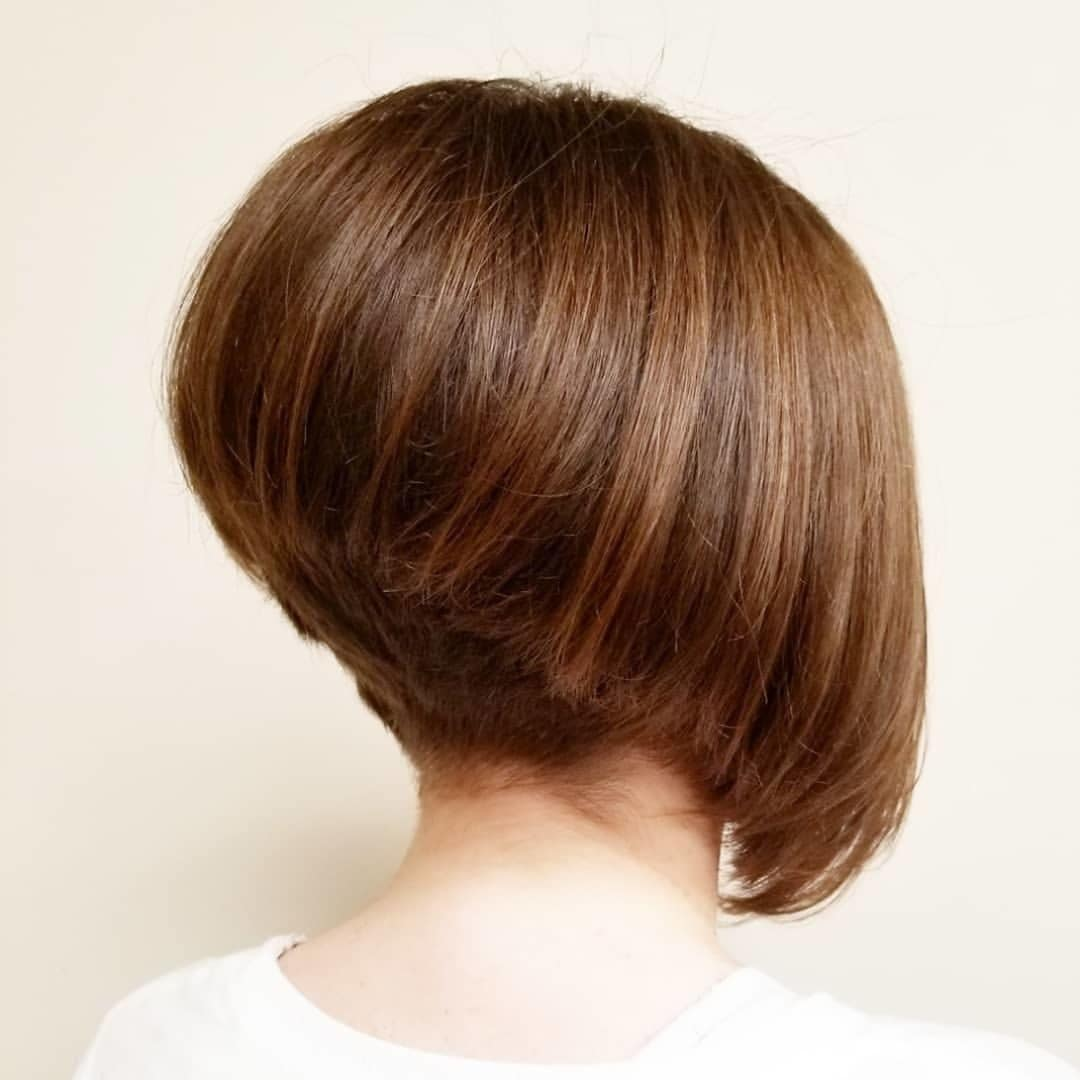 Graduated bob hairstyles: Woman with chestnut brown graduated bob with undercut hairstyle in a studio