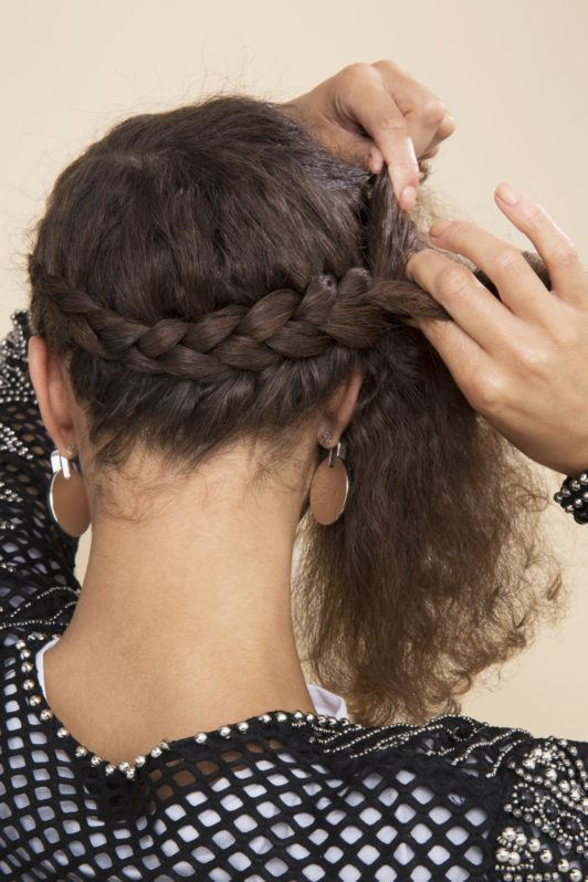 back shot of a woman with natural curly hair weaving a halo braid in the back of her head