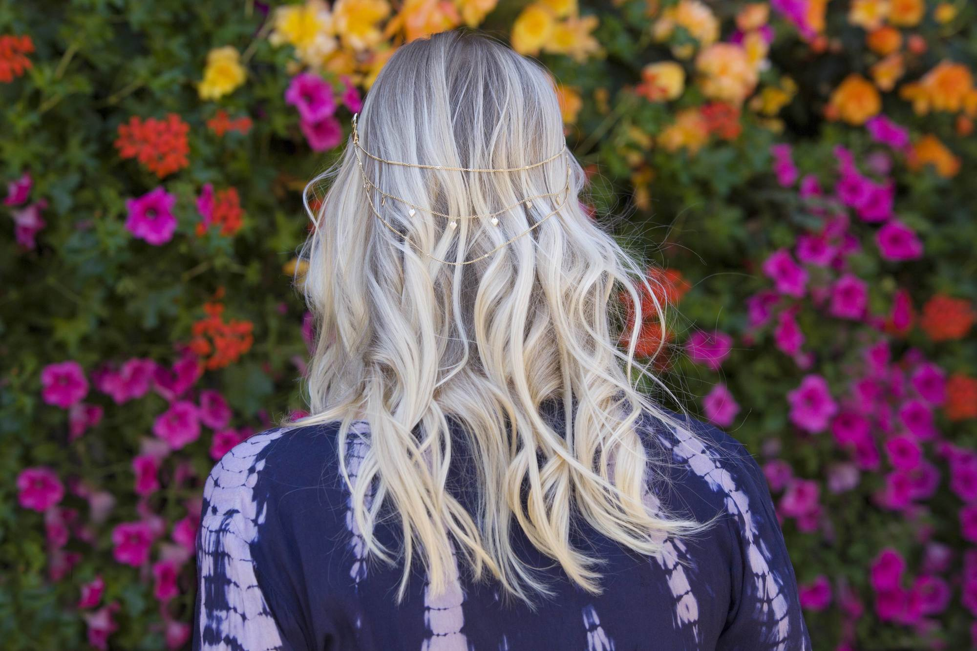 ash blonde: back of a woman's head with blonde wavy highlighted hair, complete with a festival hair accessory