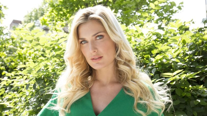 woman with long blonde hair in undone waves wearing a green dress outside