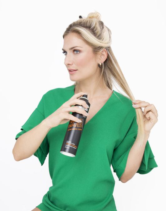 woman with long blonde hair spraying her hair with hairspray