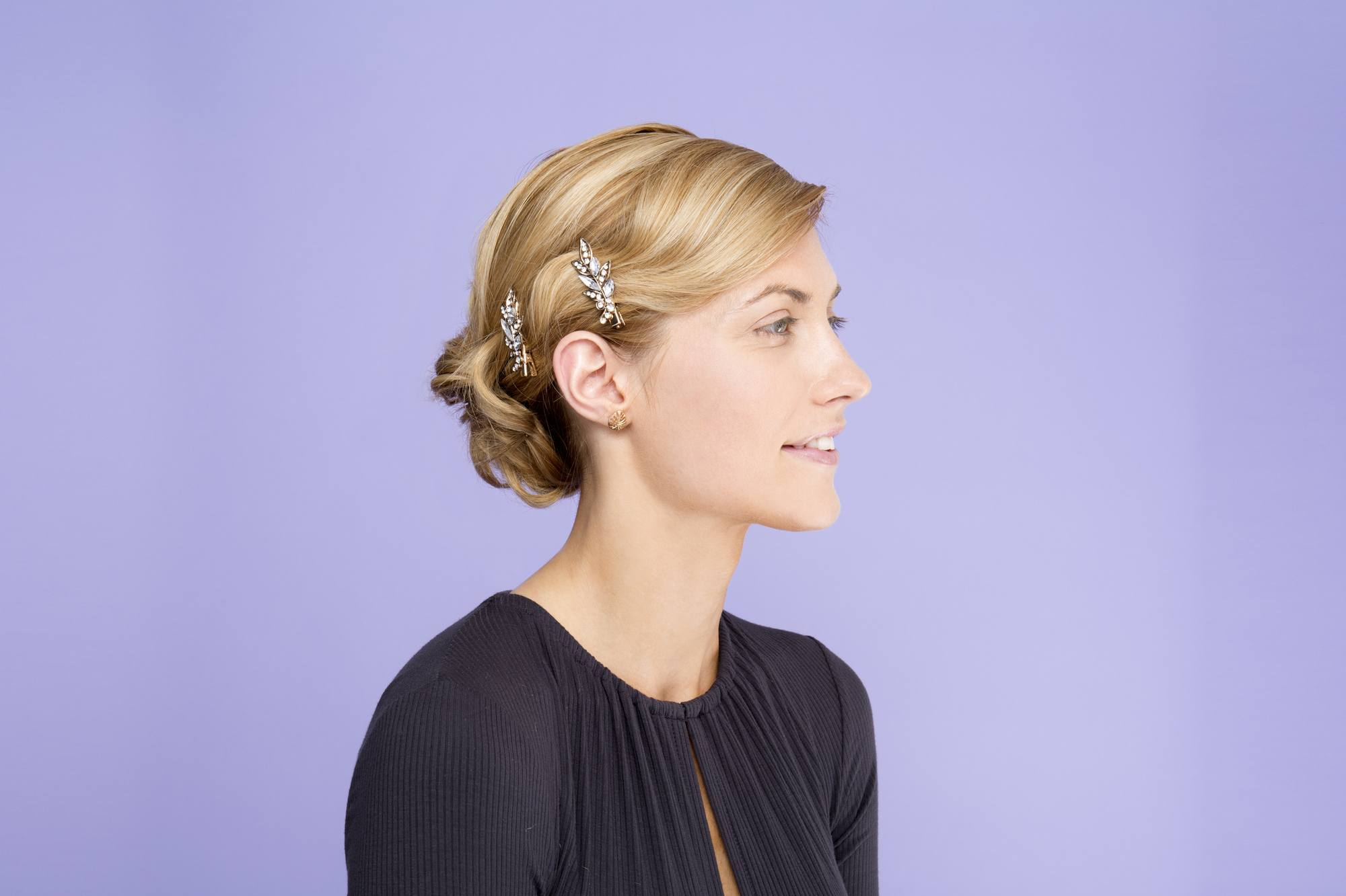Blonde hair in a side updo finished with silver jewelled accessories