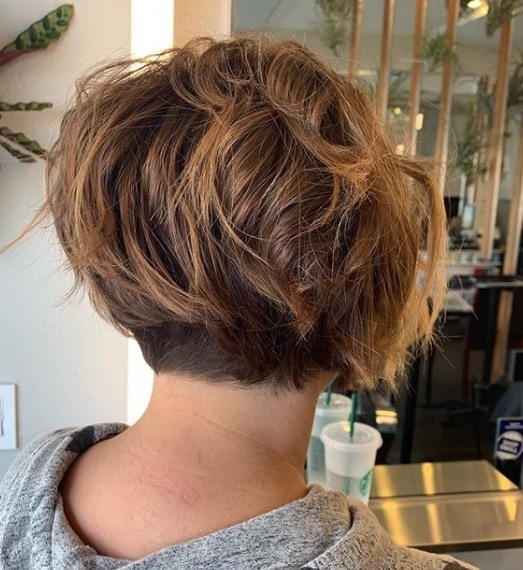 Layered bob: Back view of a woman with chestnut brown hair in a short layered bob with a shaved undercut