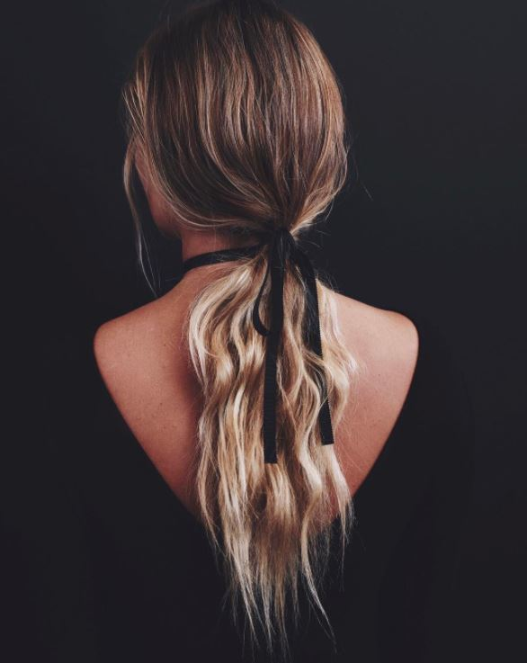 Long blonde wavy hair in low ponytail with ribbon