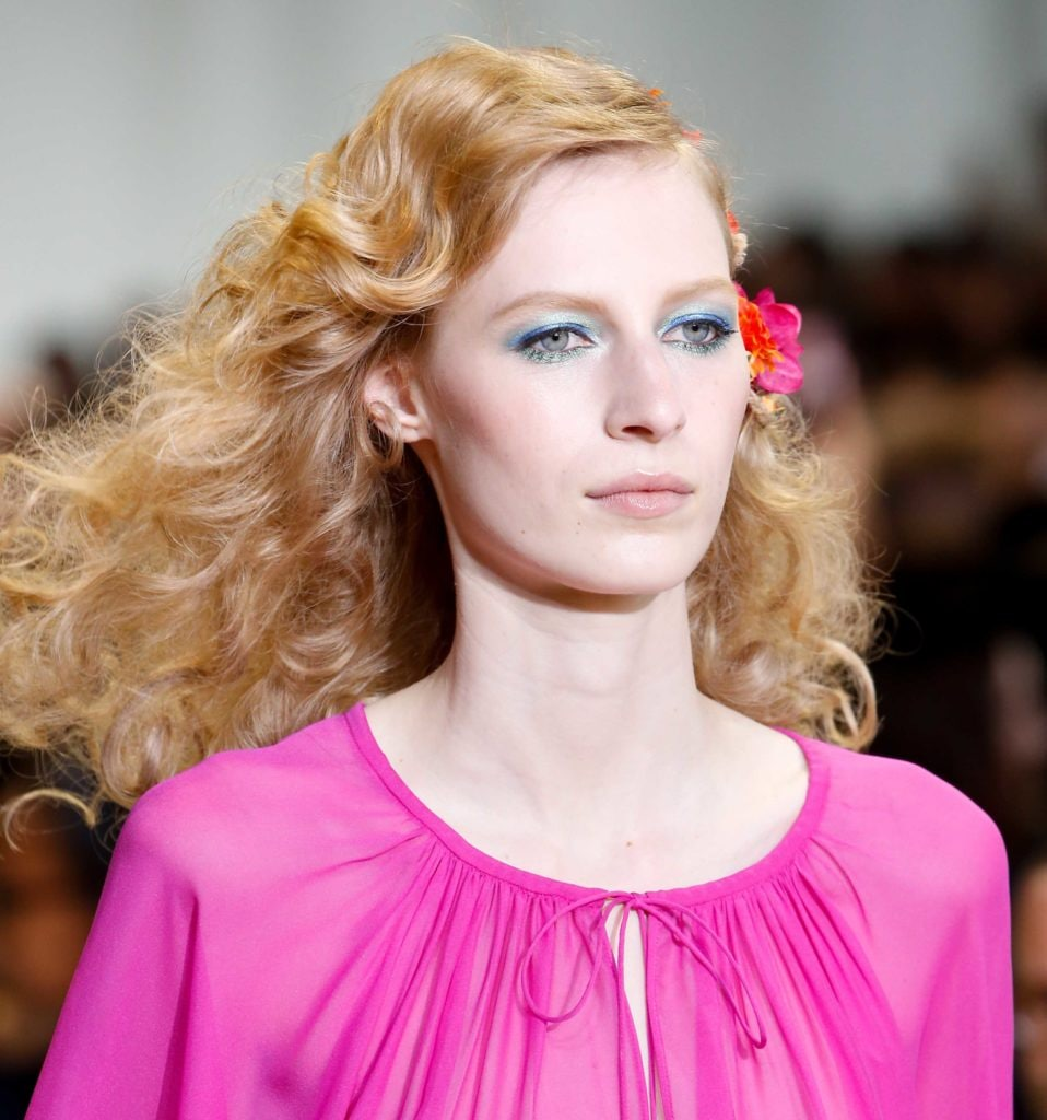DVF model with strawberry blonde hair and large bouncy curls on runway