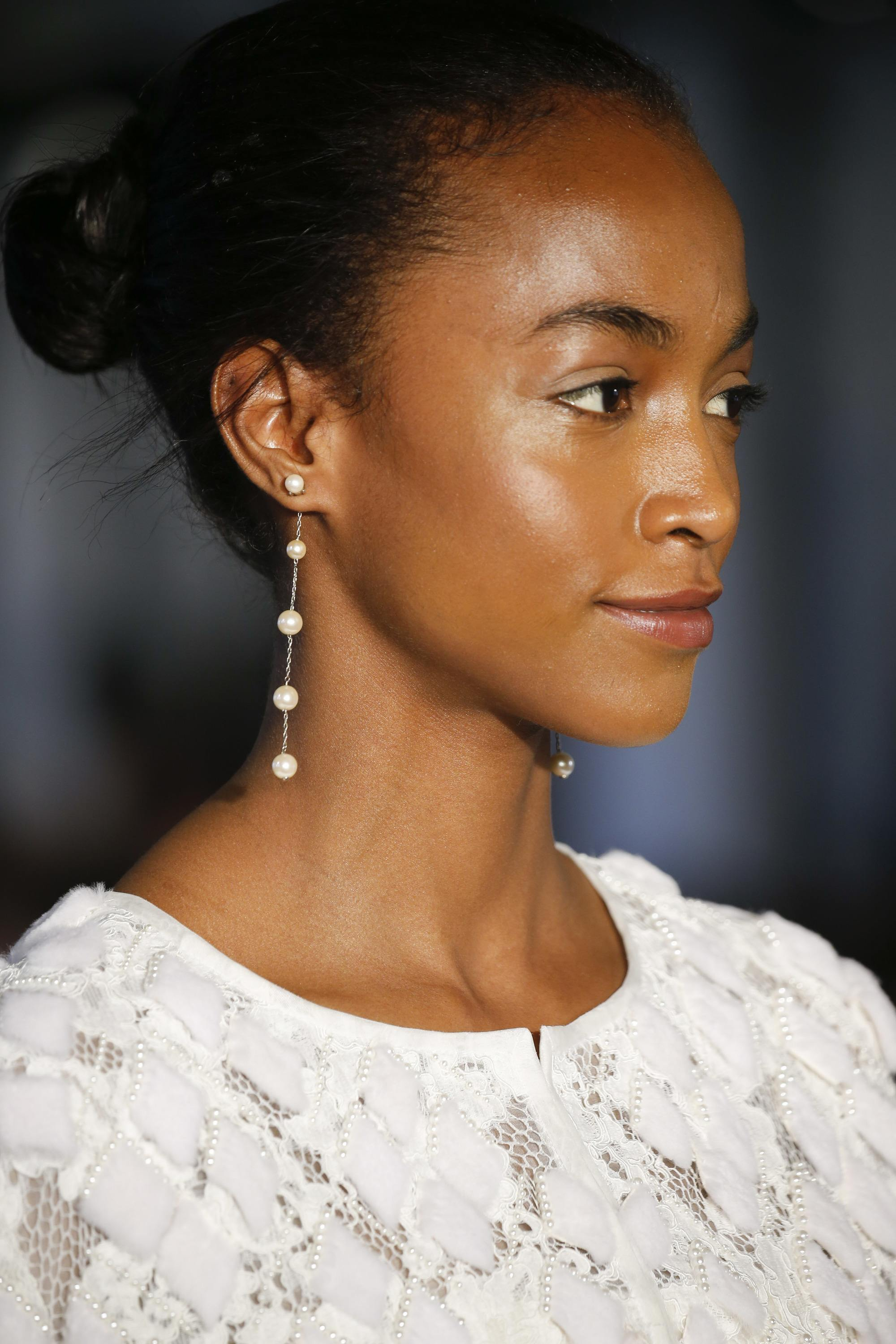 Wedding hairstyles: Model on the runway with a polished and shiny ballerina bun, wearing wedding dress with drop earrings
