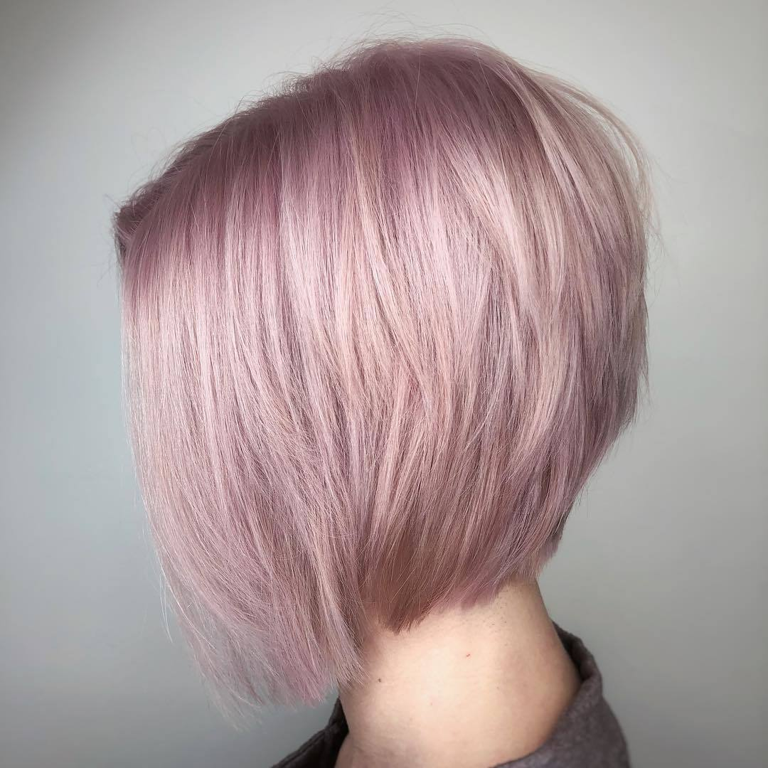 Graduated hairstyles: Woman with short graduated pink bob in a studio