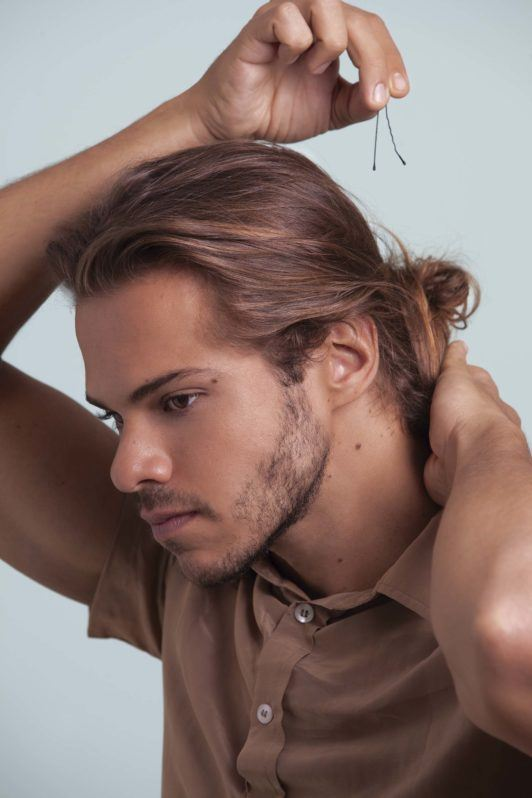a man with bun hair side looking