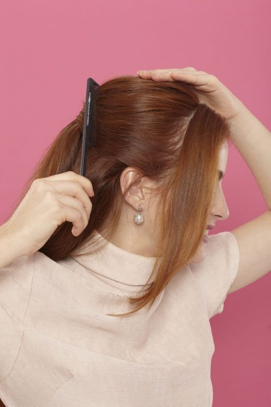 side view of a woman with auburn hair brushing back her hair