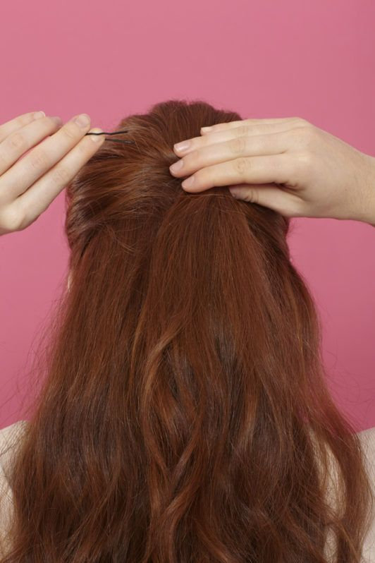 back shot of a woman with auburn hair pinning her hairstyle in place