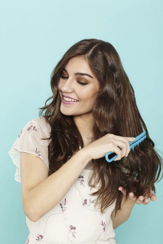 beach waves hair: woman with long brunette hair brushing through her waves
