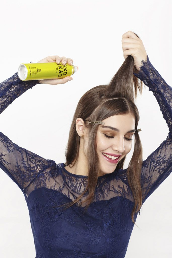 woman with long brunette hair sectioning her hair and applying a dry shampoo