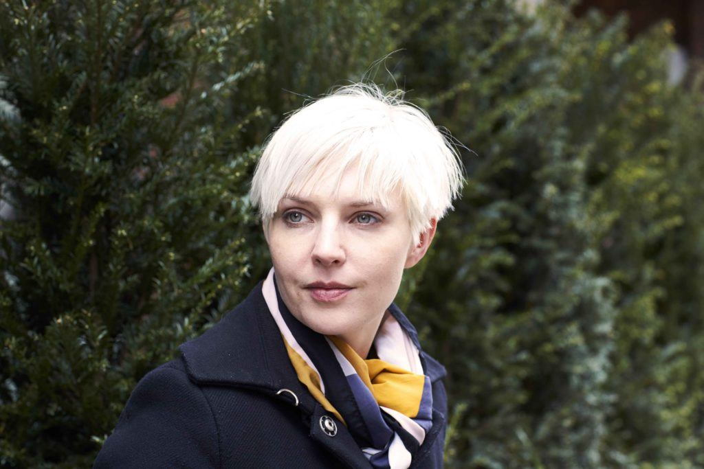 ash blonde: close up shot of woman with short, choppy Nordic blonde hair, wearing black and posing on a the street