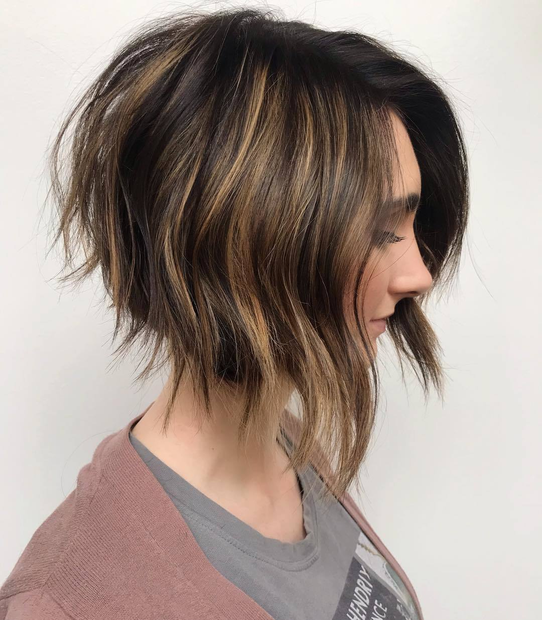 Graduated bob: Woman with dark brown graduated bob with blonde highlights with long wisps at the front