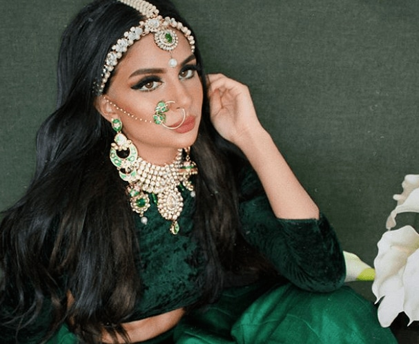 Indian wedding hairstyles: close up shot of woman with dark brown hair blown out with hair accessory on it, wearing emerald green outfit and posing in a bedroom setting