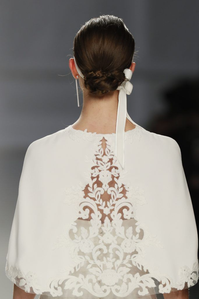 wedding updos: close up shot of model on the bridal runway with a braided low bun, complete with white ribbon around, wearing a white wedding cape and drop earrings