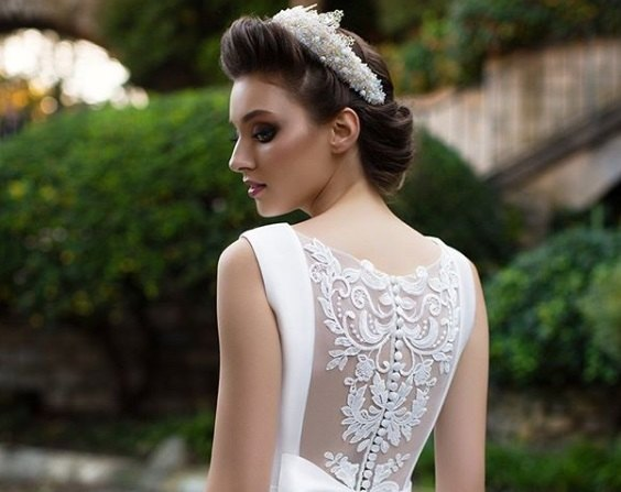 Wedding updos for long hair: Back shot of a bride with long chocolate brown hair styled into a rolled updo, complete with a pearl tiara, wearing a white dress and posing outside.