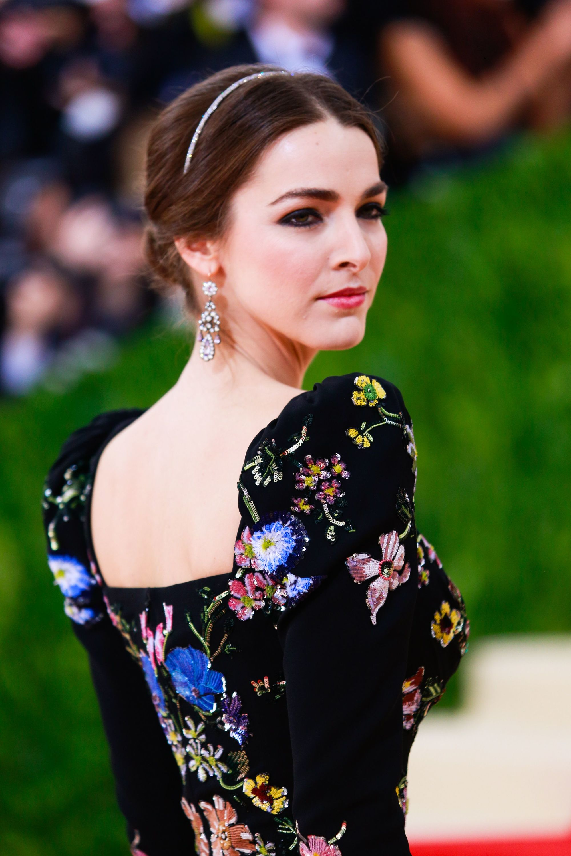 Bee Shaffer on the red carpet at MET Gala with her brown her styled in a chic updo with minimal headband.