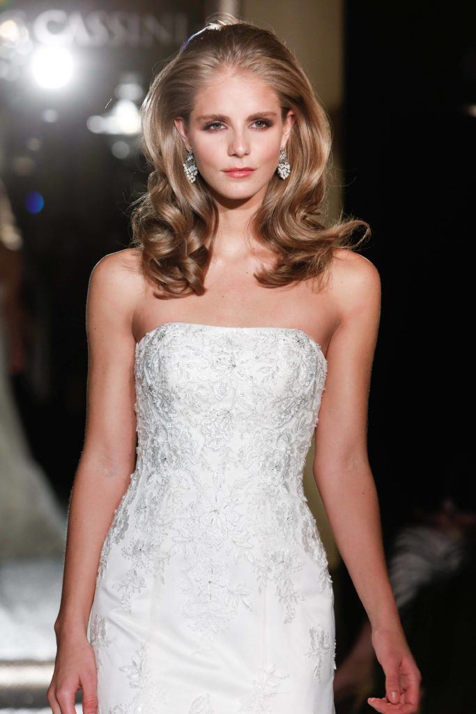 hairstyles for wavy hair: blonde model on runway with large bouncy wavy hair wearing strapless wedding dress
