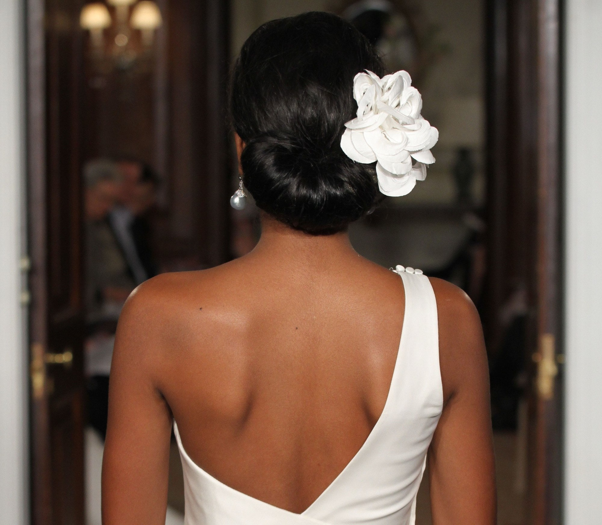 bridal updos: close up shot of model on the bridal runway with low rolled updo with a flower in it, wearing white open back wedding dress