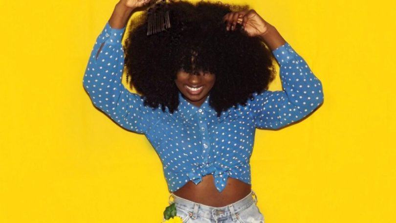 alexus crown with afro hair wearing blue shirt and jeans