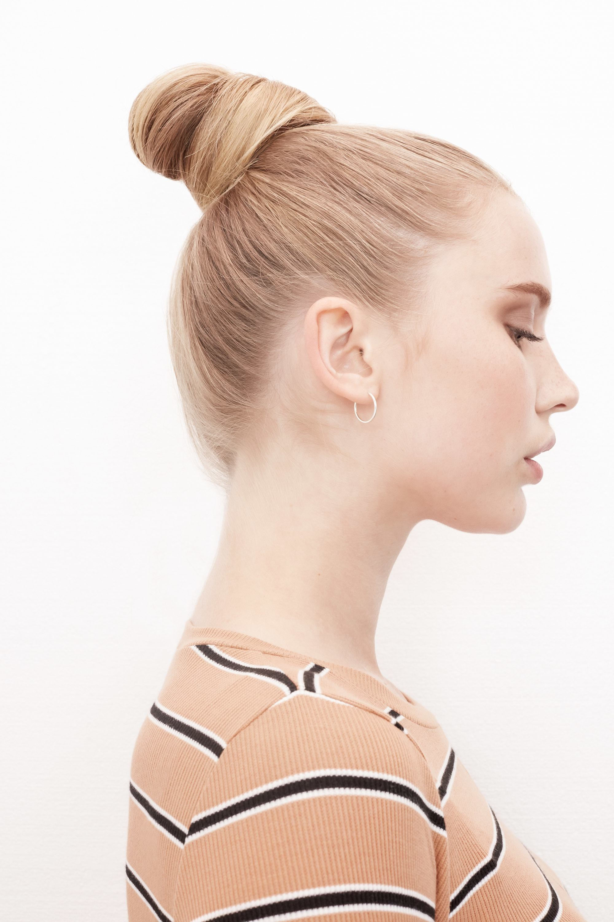 Blonde woman with a top knot hairstyle
