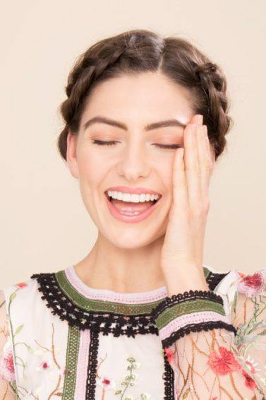 Boots x ATH simple holiday hairstyles: Happy brunette model with halo braid, wearing a floral dress