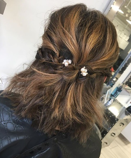 woman with a brunette bob with highlights styled in a half up half down braid