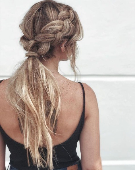 Boho hairstyles: Back view of a woman with ash blonde long hair in a braided ponytail style