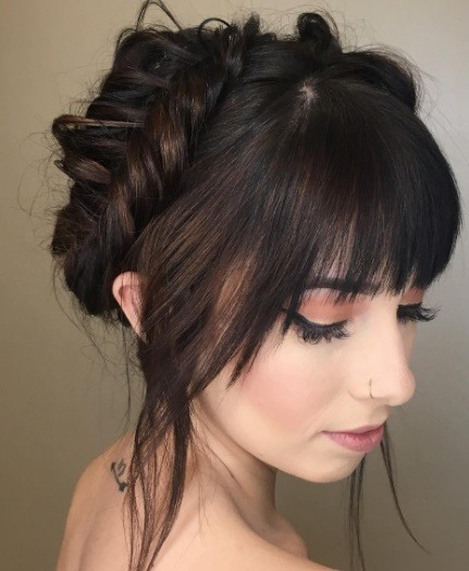 Wedding updos for long hair: Close up shot of a woman with long dark brown hair and bangs, styled into a fishtail crown braid updo.