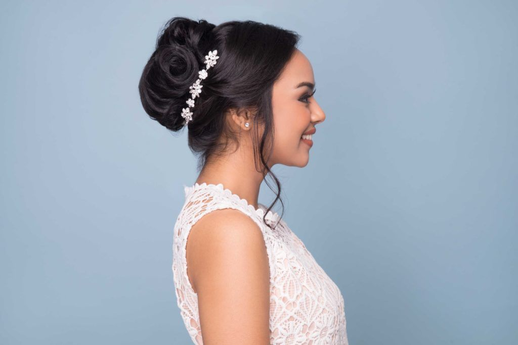 wedding updos: close up shot of model with donut bun updo, with a floral headband around it, wearing wedding dress and posing in a studio