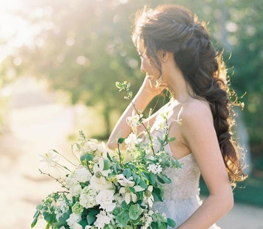 Wedding updos for long hair: Side shot of a bride with long brown hair styled into intricate braided ponytail, wearing a white dress and holding flowers, posing outside.