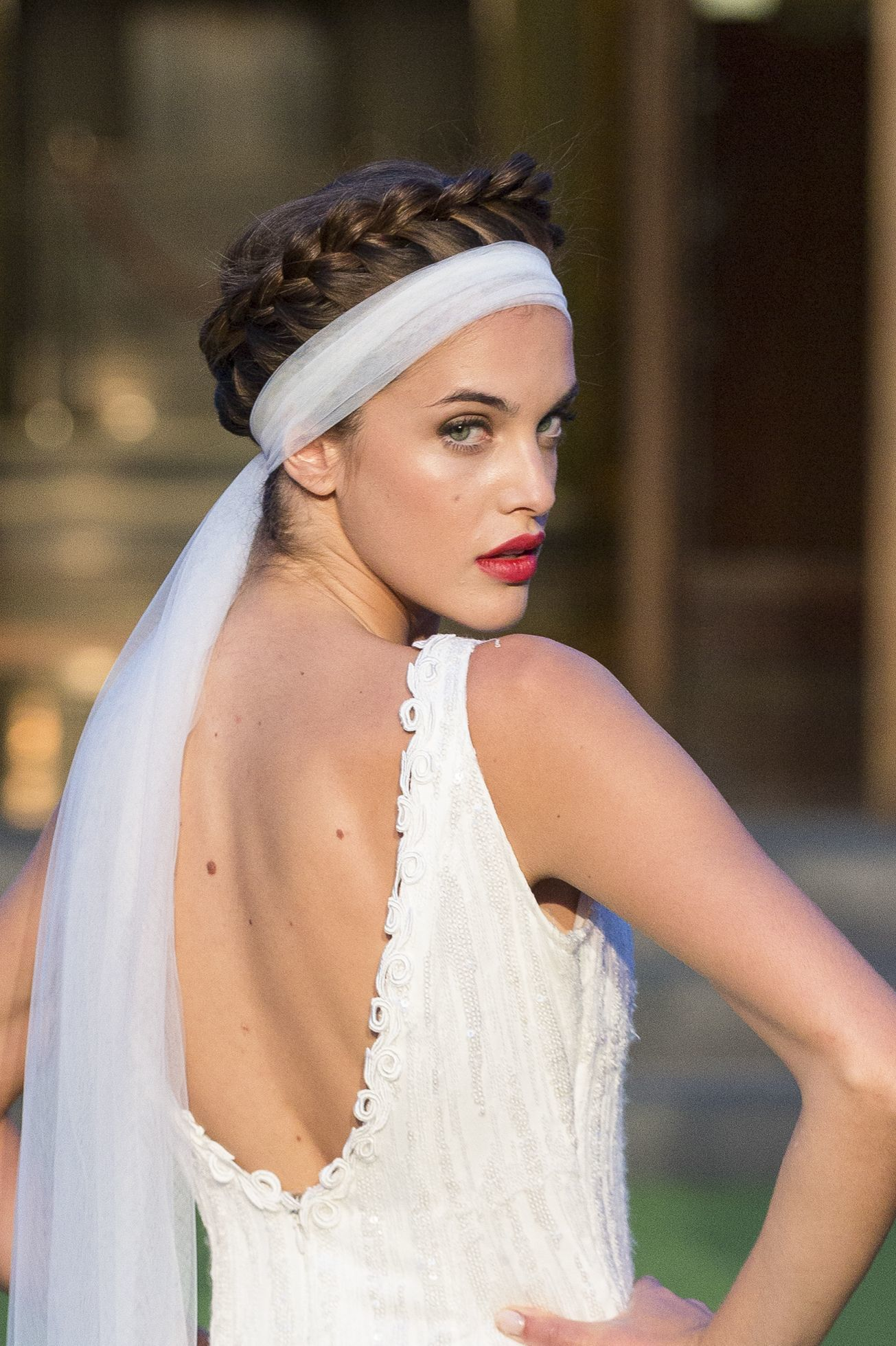 wedding updos: close up shot of model on the bridal runway with crown braid hairstyle, with a veil wrapped around it, wearing white dress and posing