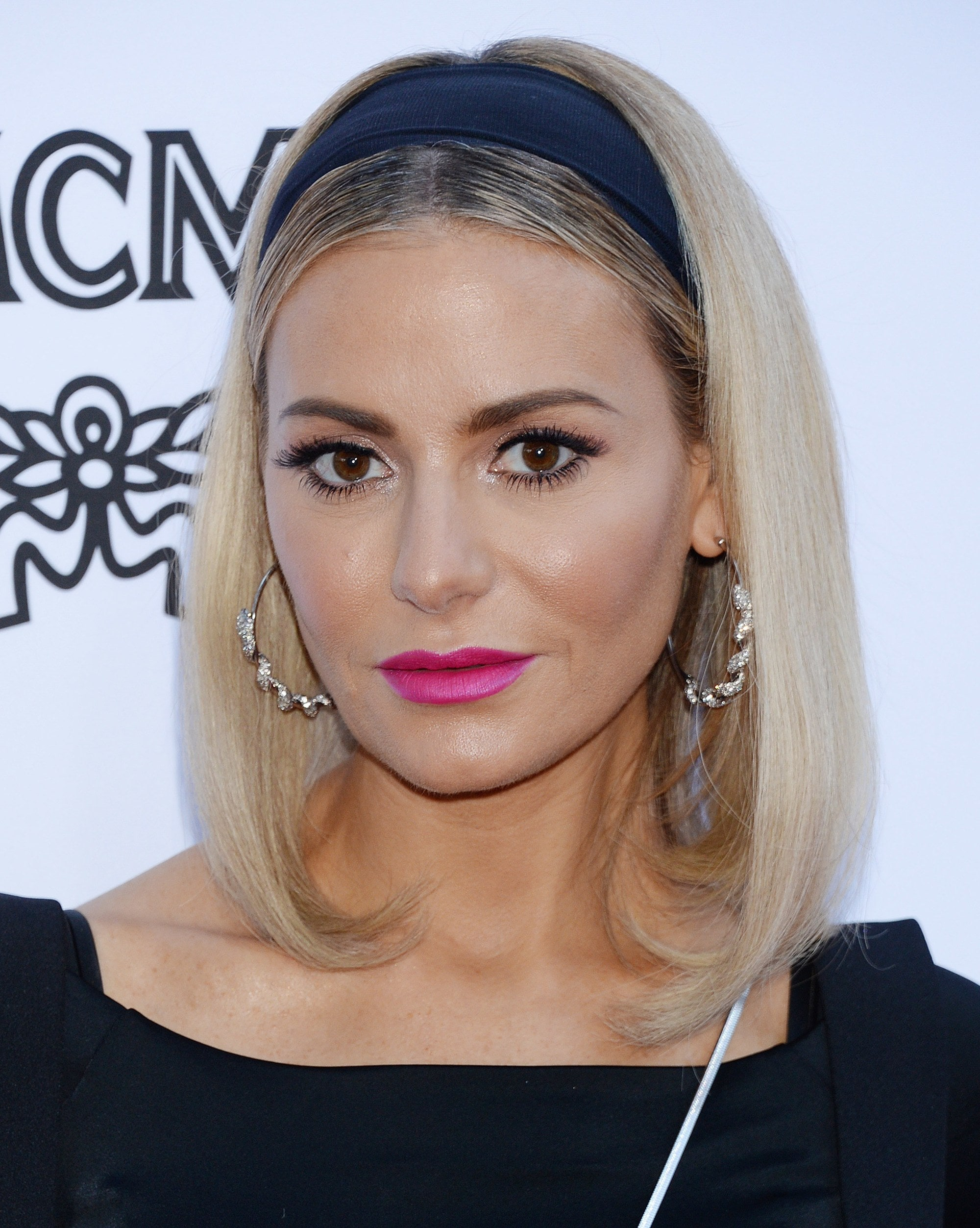 Dorit Kemsley with blonde straight shoulder-length hair, styled with a black headband