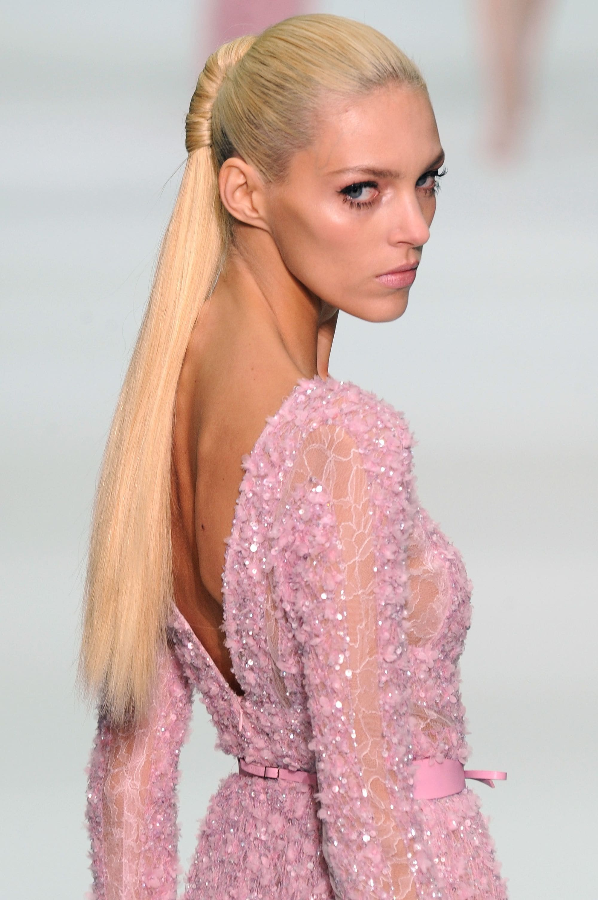 blonde elie saab model on the runway in a pink dress with a structured ponytail