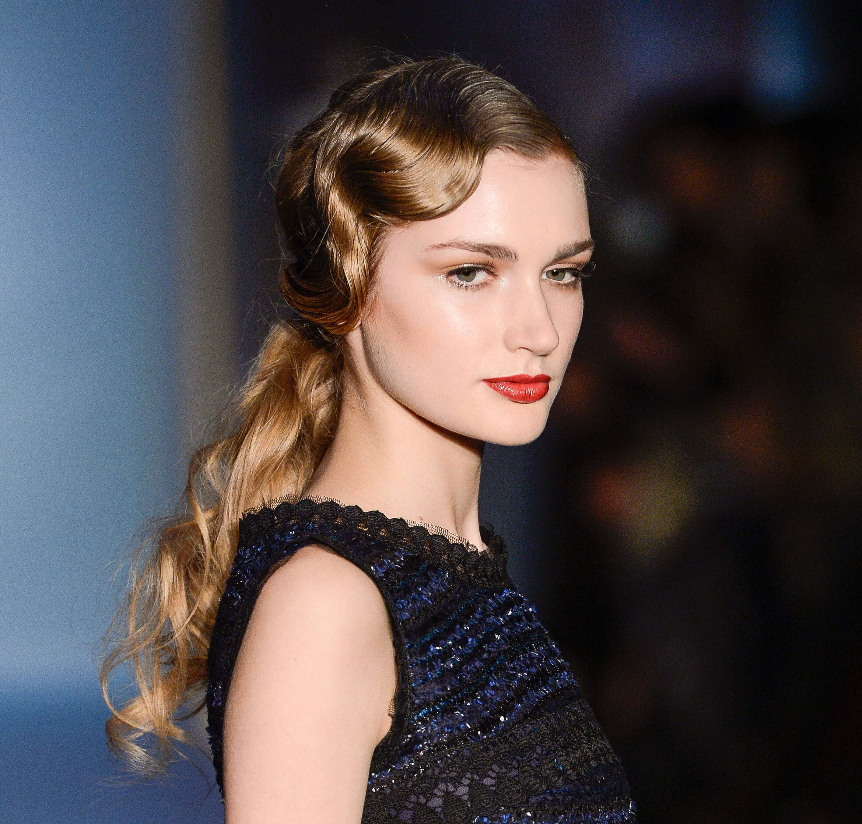 model on runway with golden brown dark blonde long wavy hair styled in a retro finger wave finish