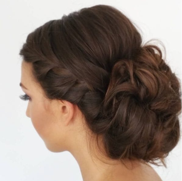 brunette woman with her hair in an updo with braided bang details