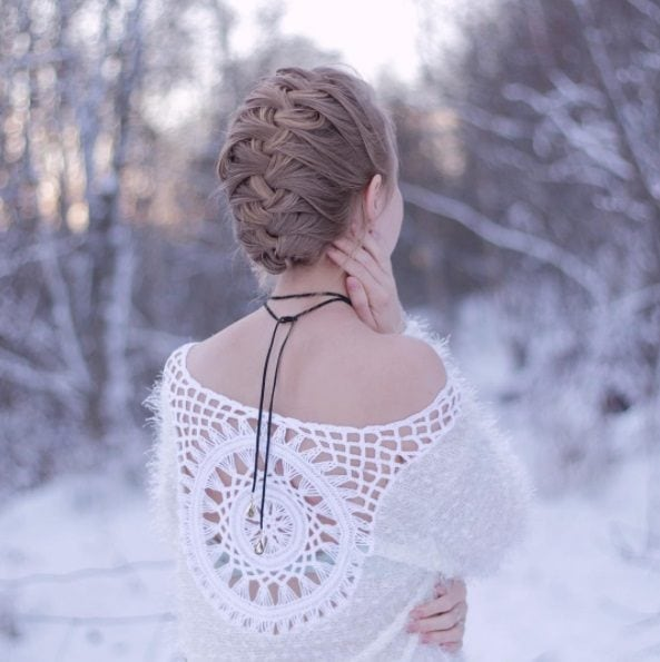 blonde woman standing in the snow with her hair in a french braid mohawk style